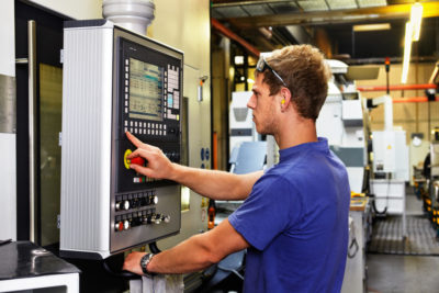 skilled worker controlling a digitally programmed machine tool